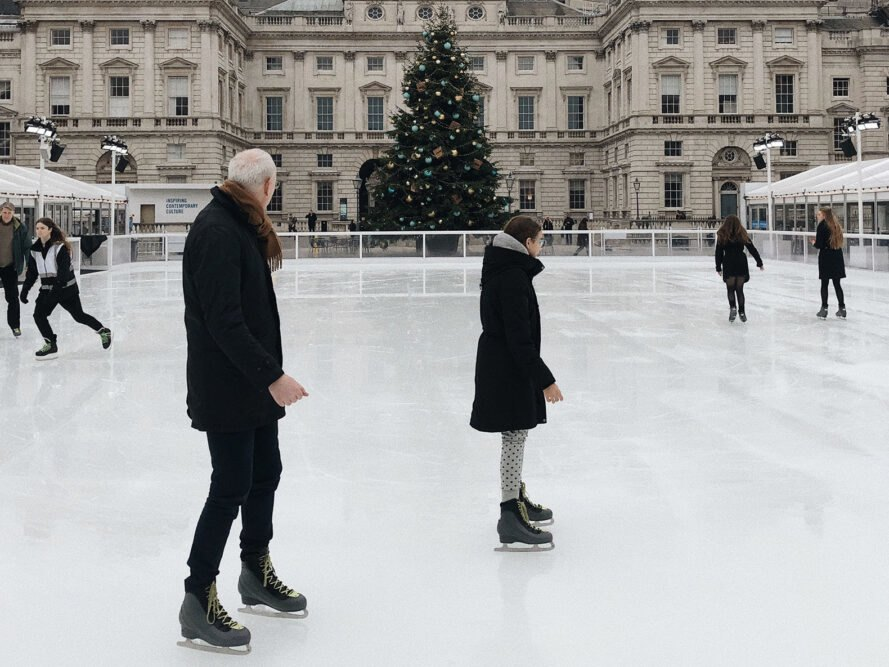 people skating in an ice rink with a building and Christmas tree in the background