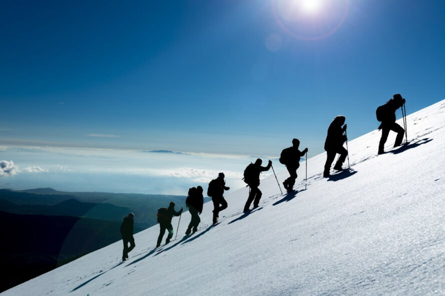 group of people climbing snowy mountain