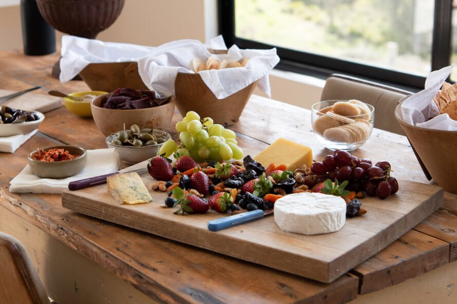 wood board with cheese, dried fruits and grapes