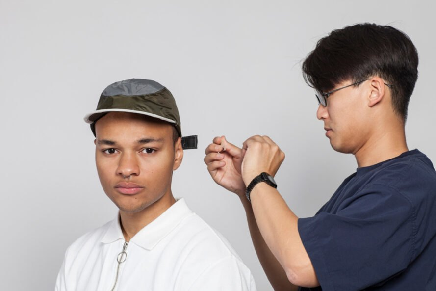 designer tightening a hat on a model