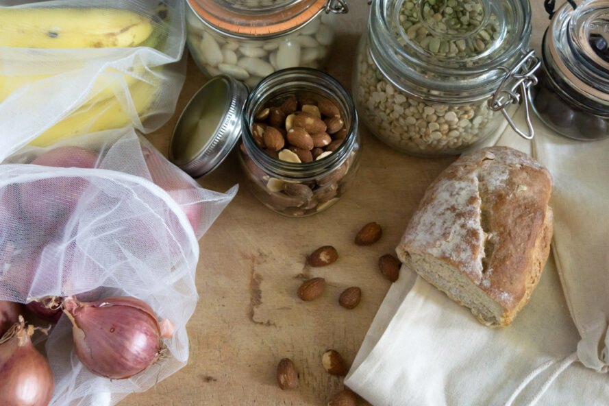produce in reusable mesh bags and glass jars filled with nuts and seeds