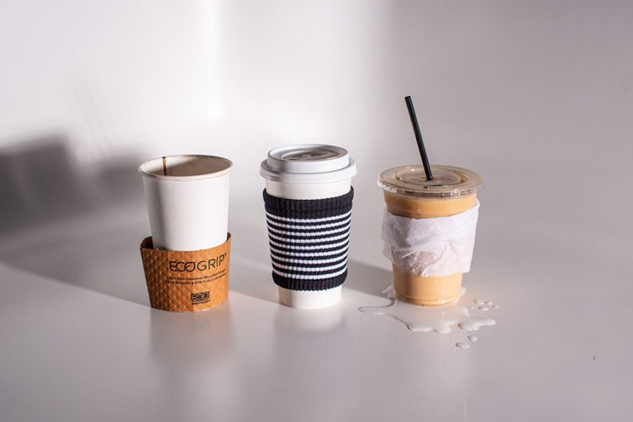 one coffee cup wrapped in cardboard sleeve, one cup wrapped in a napkin, and one cup wrapped in cloth coffee sleeve