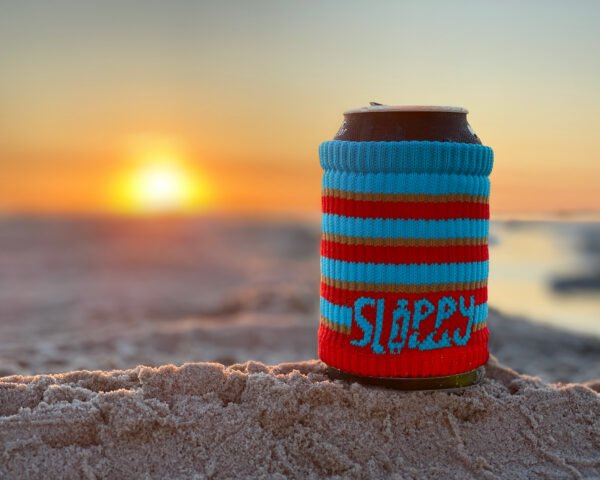 drink can wrapped in red and blue cloth cup sleeve on a rock with sun setting over the ocean in background