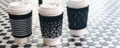 three coffee cups wrapped in black and white cloth cup sleeves