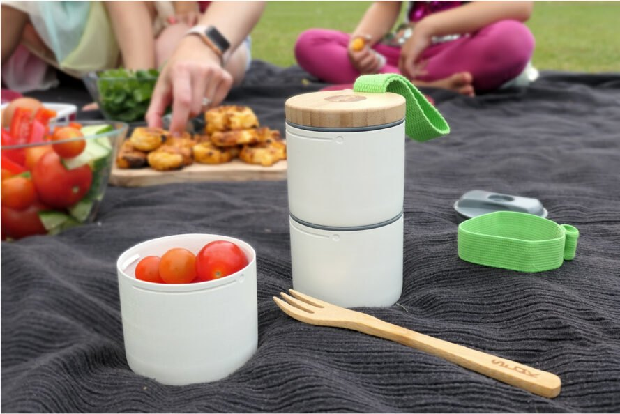 stacked white containers with snacks on a picnic blanket