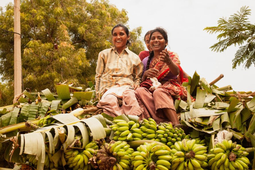 two women sit on top of a pile of bananas and banana leaves
