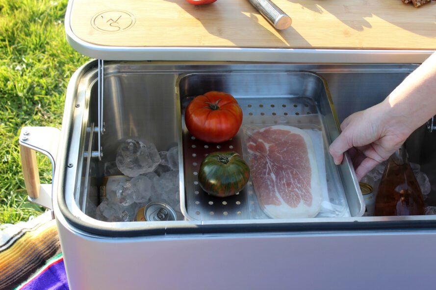 steel container holding meat and tomatoes inside a cooler