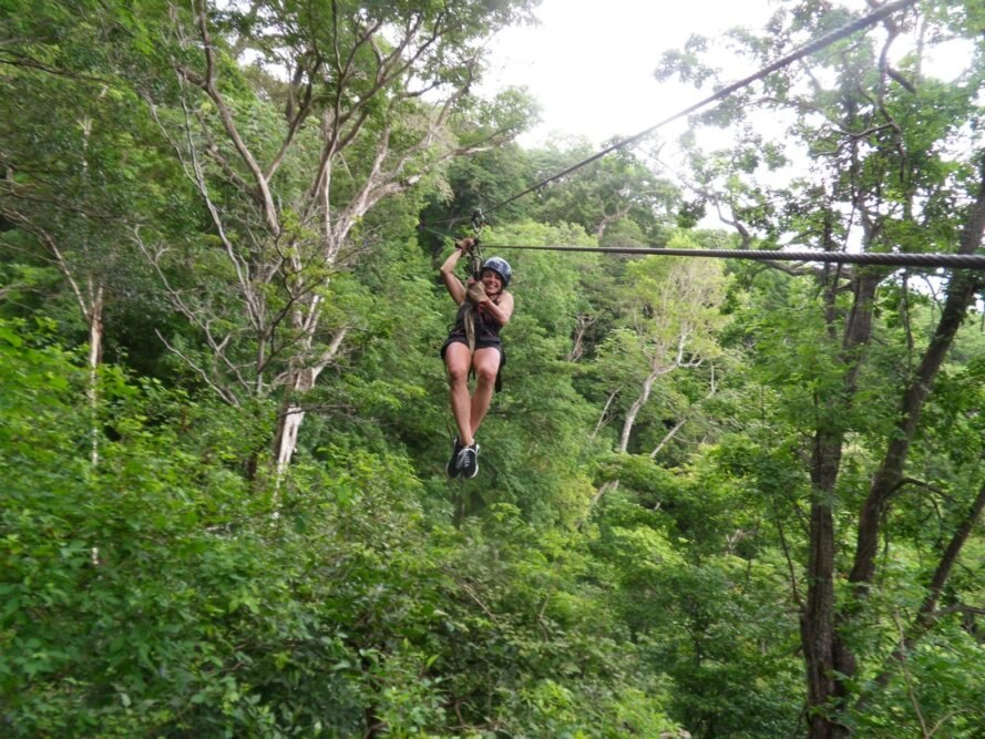 person smiling and zip lining