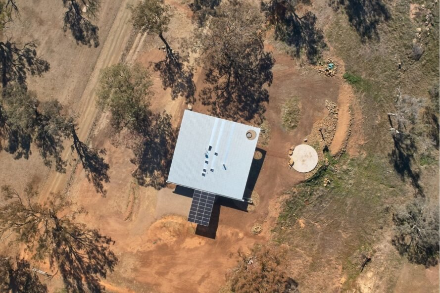 aerial shot of square home surrounded by dry fields