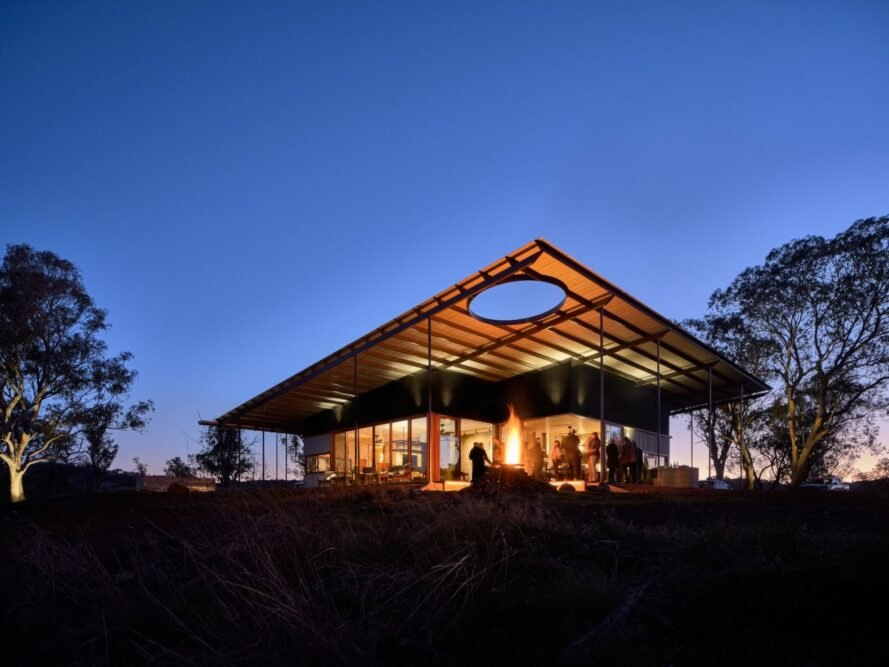 low-lying home with extended roof lit up at night