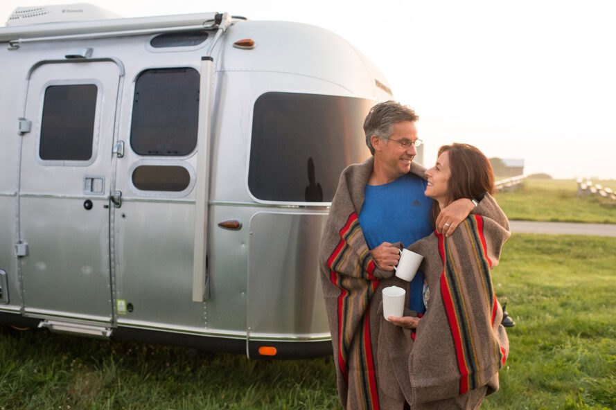 two people in front of an airstream, with a blanket around their shoulders