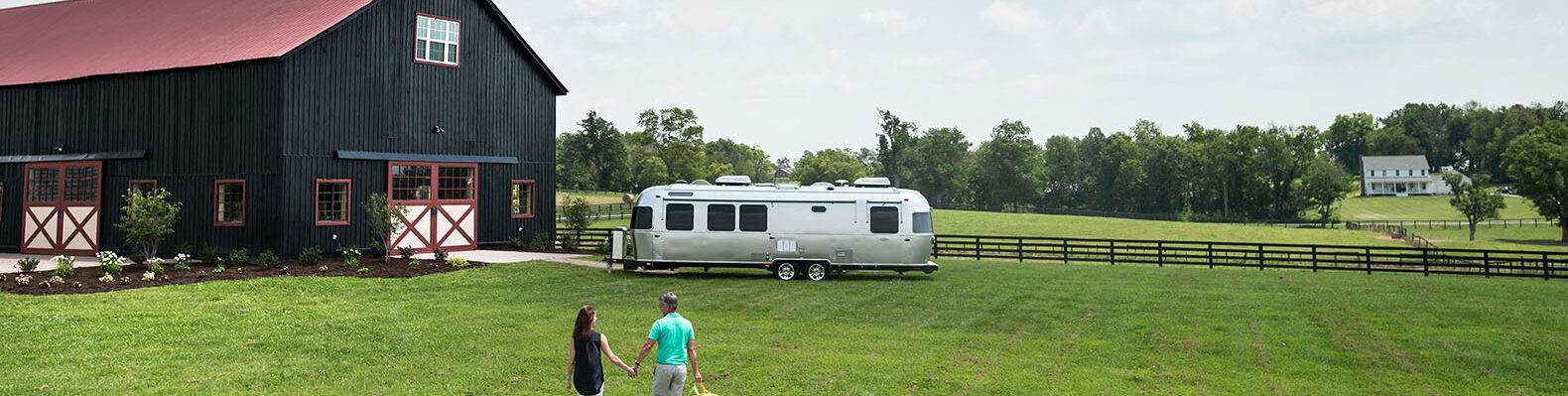 two people walking towards an airstream with a barn-like structure next to it. they are walking on a green field