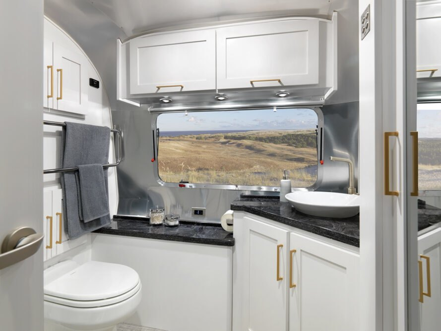 bathroom inside interior layout of 2020 Classic Airstream, with window looking out onto a field