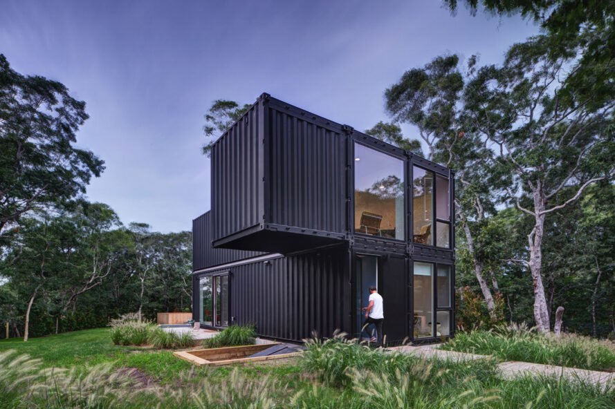 two-story black shipping container home