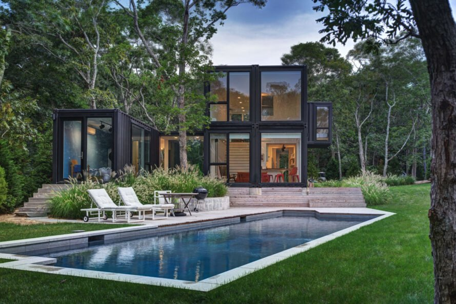 large swimming pool near black shipping container home