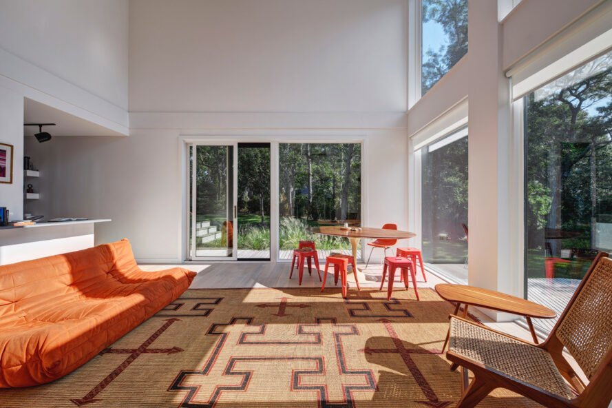 living room with double-height ceilings and orange furniture