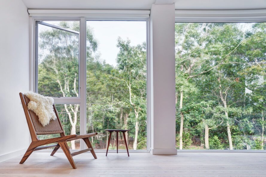 small wood chair beside glass wall