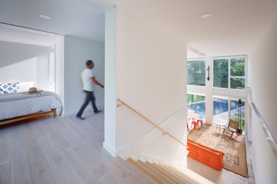 wide staircase leading from living room up to a bedroom