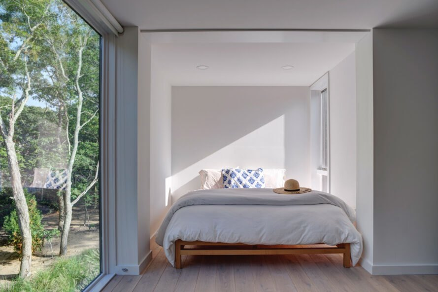 white bedroom with a glass wall