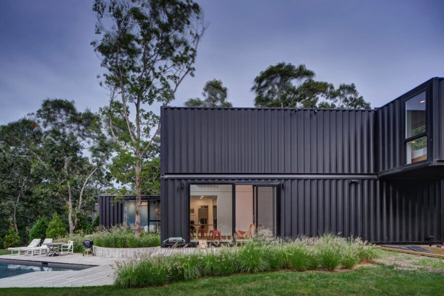black shipping container home with sliding glass doors leading out to a patio