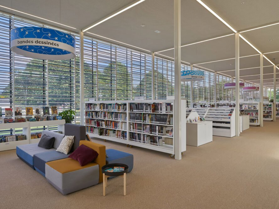 the interior of the library, with shelves of books and colorful overhead signs marking off different sections of the library. a section of sofas sit in front of one shelf. the seating is multi-colored