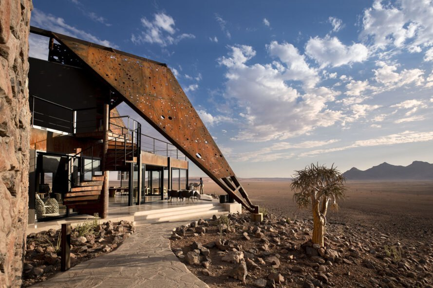a large triangular roof-like structure covers a small patio area in the desert