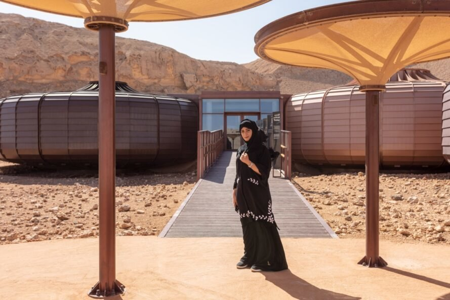 a person in what appears to be a black chador, standing in front of a building with two circular structures