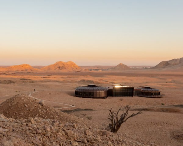 a desert landscape with a dark building composed of three structures
