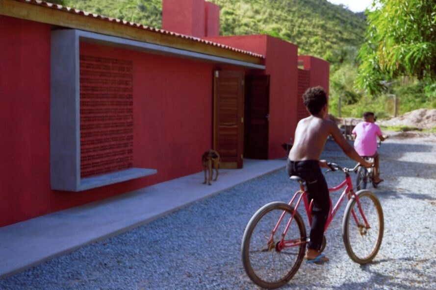 a red building to the left, white a dog standing in front of it. to the right, two children ride bikes.