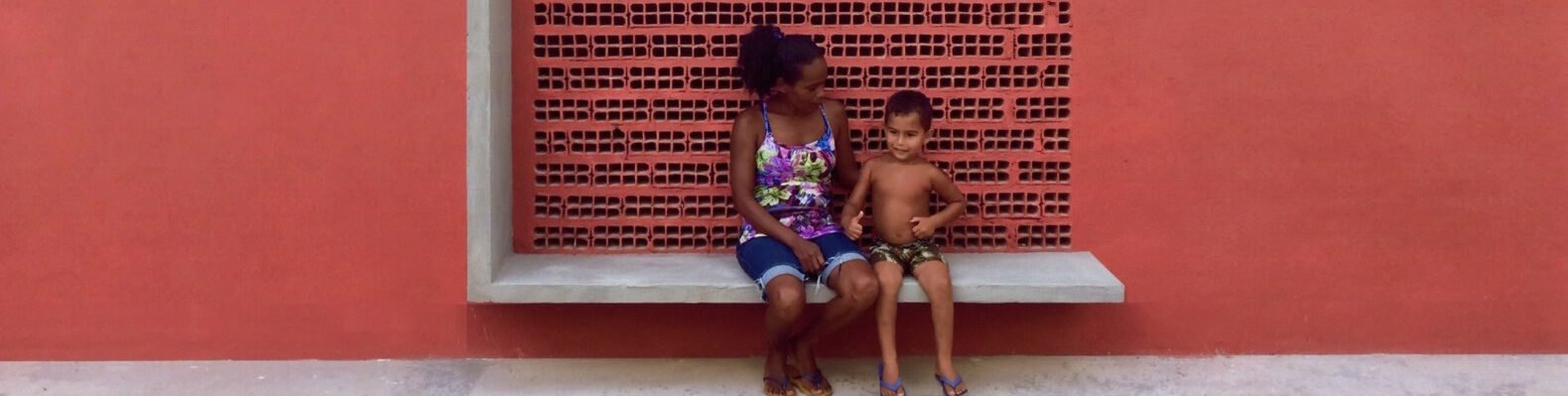 a red wall with a bench structure that a woman and child are citting on. a square cut-out behind them has a dotted pattern on the wall