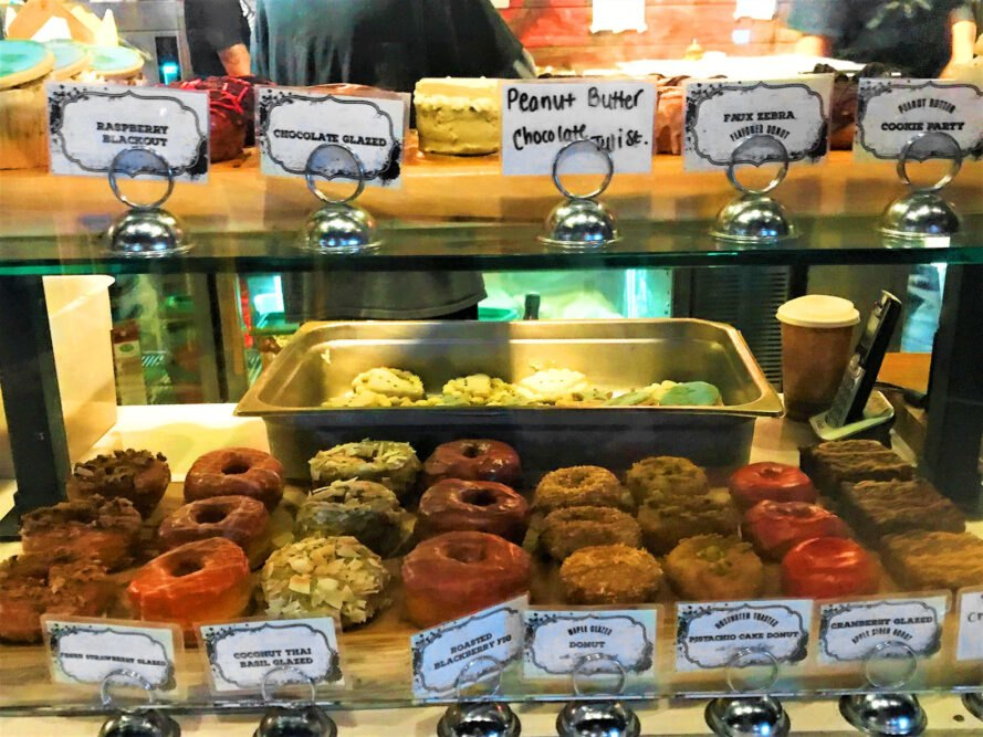a bakery case full of various flavors of vegan donuts