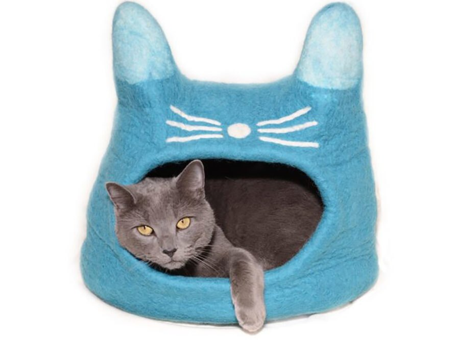 a gray cat lounging in a light blue, felt cat house shaped like a cat-head with ears