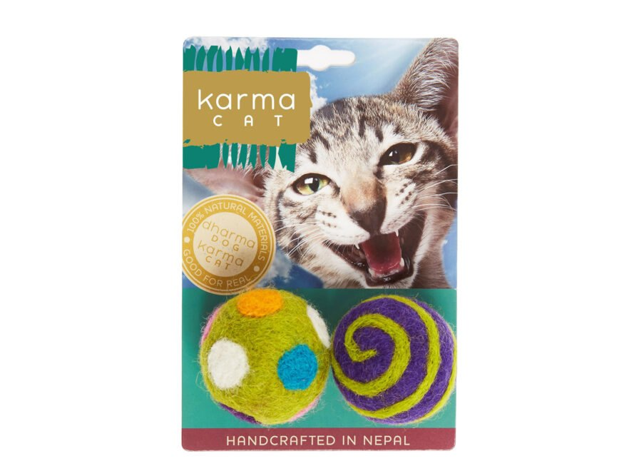 a Karma Cat toy package with two felt balls, on that is green with multicolored dots, and on with green and purple spirals. the packaging features a light gray speckled cat bearing its teeth