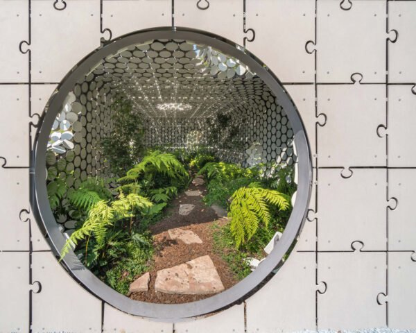 a close-up view of the circular entrance leading into the short gray building. inside the building are walls composed of circular cut-out shapes. also inside is a stone path through a lush, green plant-filled area.