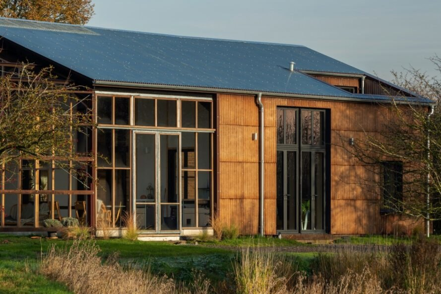 pitched-roof home with large wall made out of glass panels