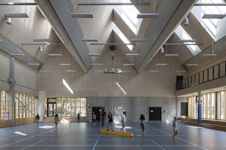 kids in gymnasium with pitched ceilings and skylights