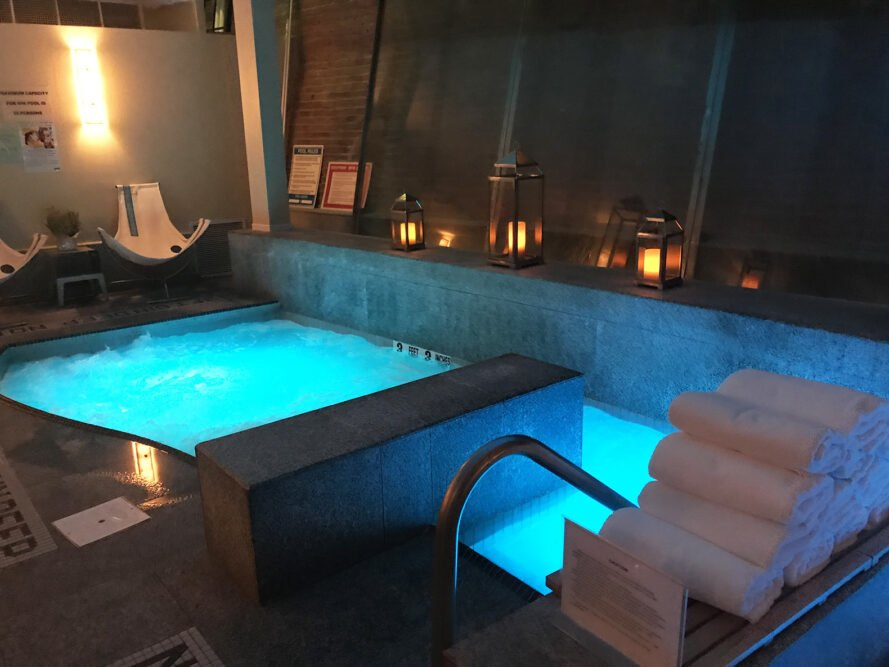 a hot tub area with bubbling water lit up with blue lights. white towels are stacked off to the side.
