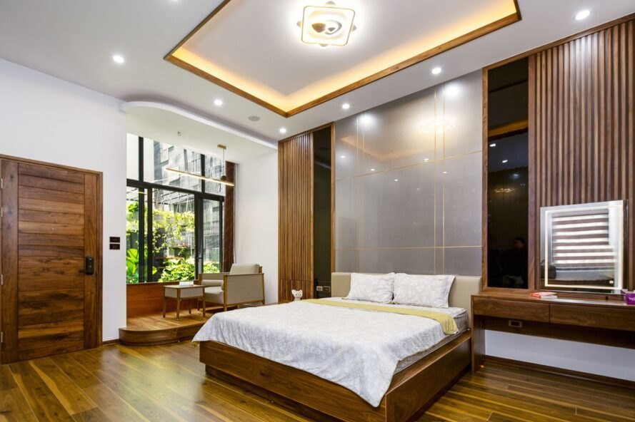 white bed on wood platform in large white room