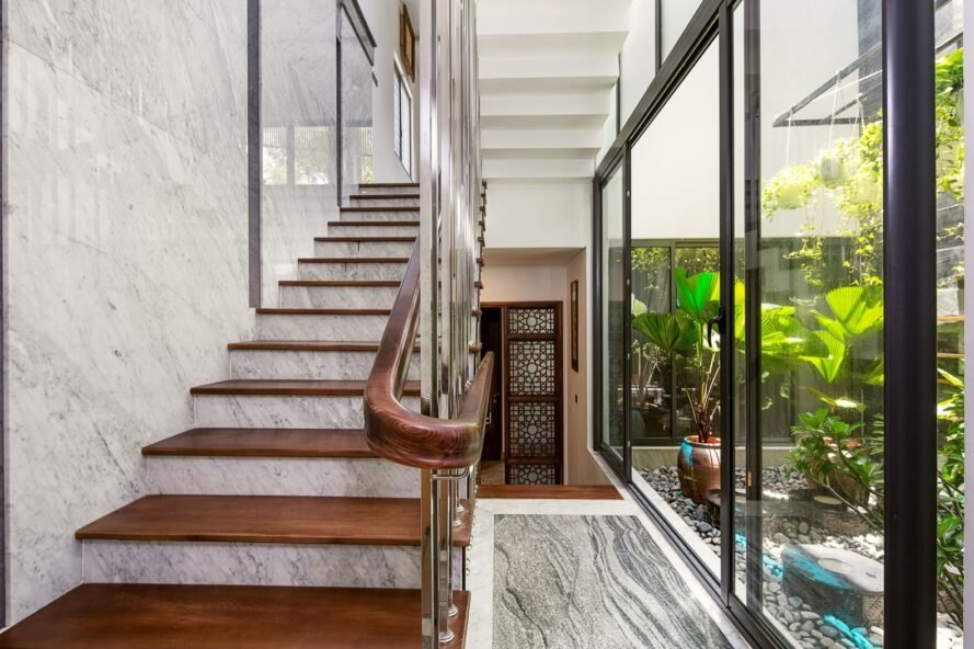 open glass wall beside a wood and marble staircase