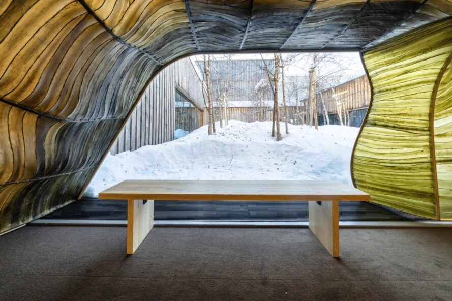 wood bench near pavilion opening revealing snowy views