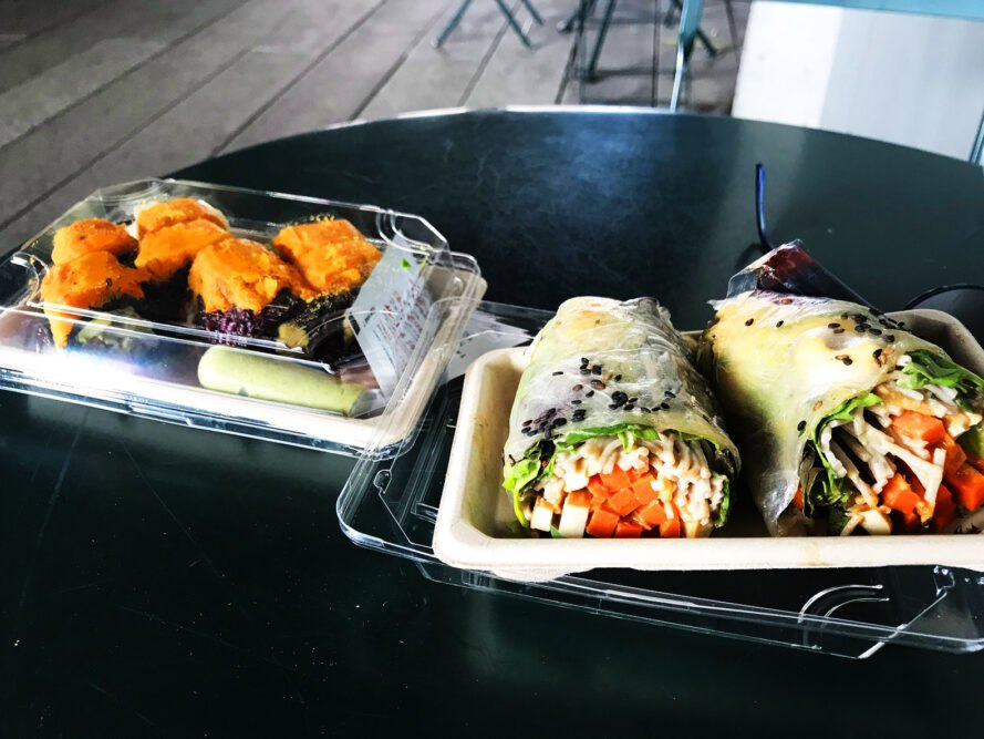 a table with two trays of food. the tray to the right has a roll full of bright veggies and the tray to the right shows orange-colored vegan sushi