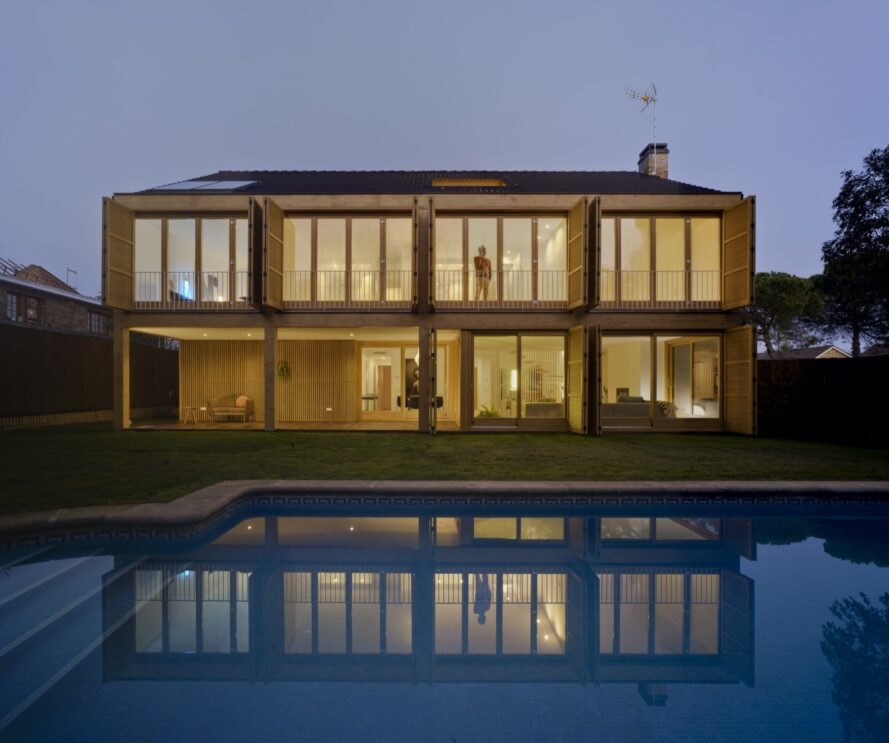 tan home with several large windows lit from within at night