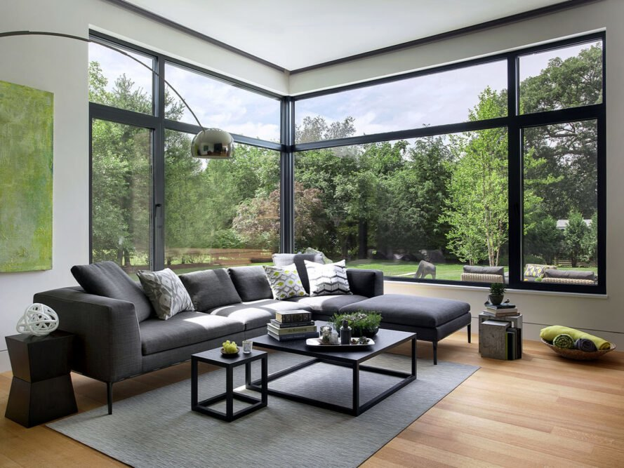 a living room with black sofas, two tables, a lamp and large floor-to-ceiling windows