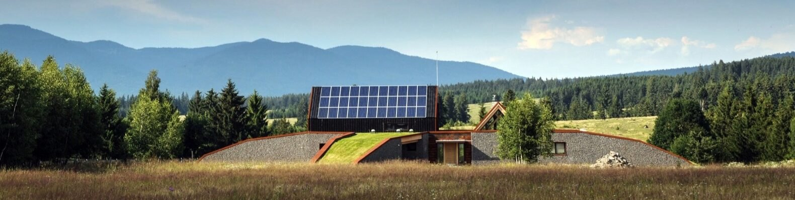 a far view of the entire house. a field is in front of the building. a lane of bright green lawn leads up to a structure covered in solar panels. to the right is a textured gray semi-cricle structure. in the background are mountains and trees
