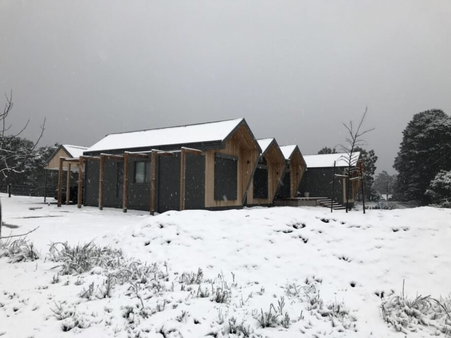 wood and dark gray gabled building in a snowy landscape