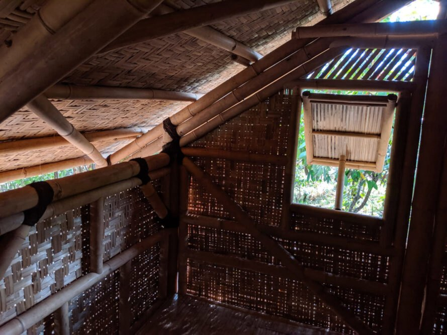 the interior of a bamboo house with a window covering open to look outside at trees