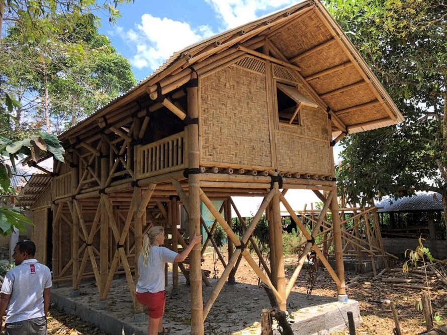 a bamboo house on bamboo stilts that are cross braced and attached to what appears to be a concrete foundation. surrounding the house are green trees and two people, one who is looking to the left and another who is touching one of the bamboo stilts
