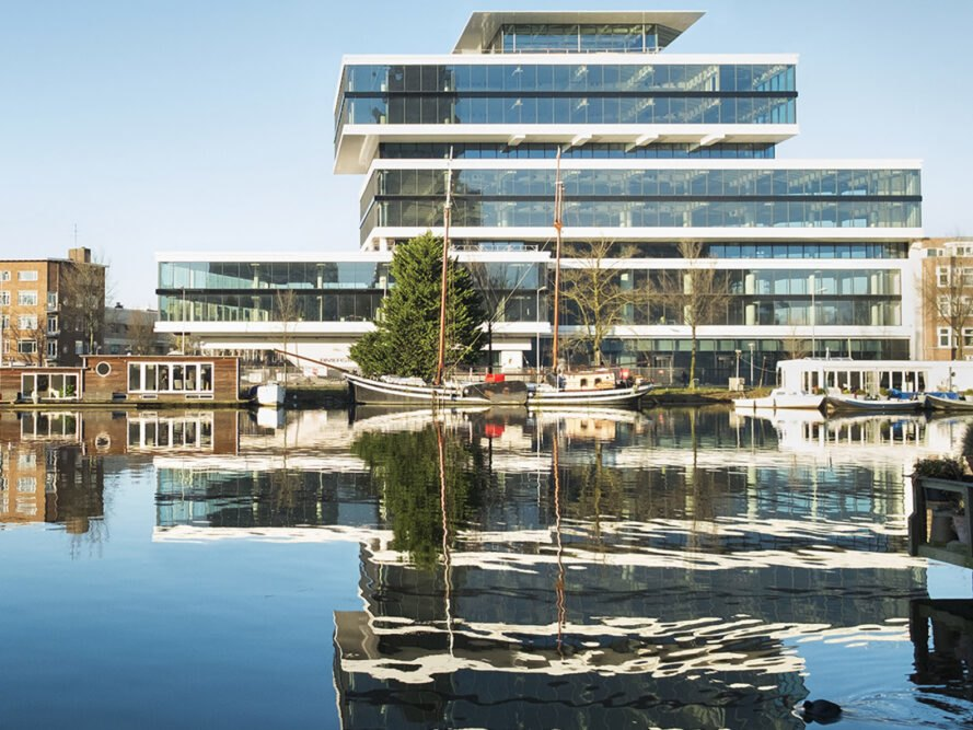 a riverfront view of a tired, glass facade building, which is also reflected in the water