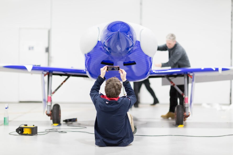 a person sits on the floor in front of a blue plane, taking a picture of it on a phone