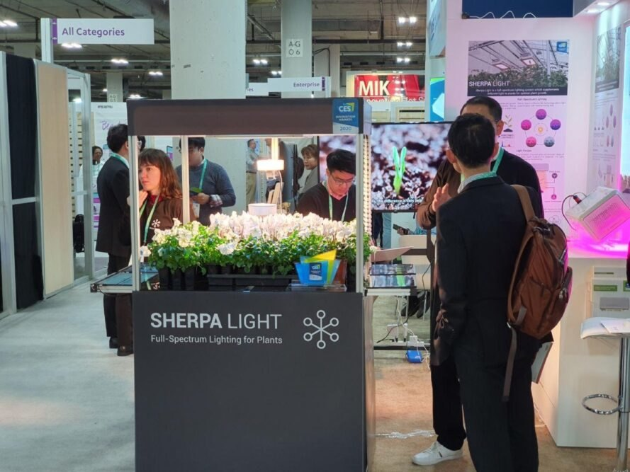 """a picture of a Sherpa Light booth at CES 2020. green plants are mounted on a gray box labeled """"Sherpa Light."""" people surround the booth."""